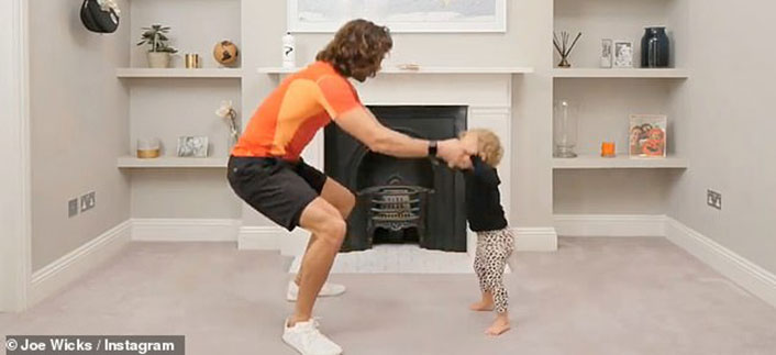 Adult and toddler exercizing in living room