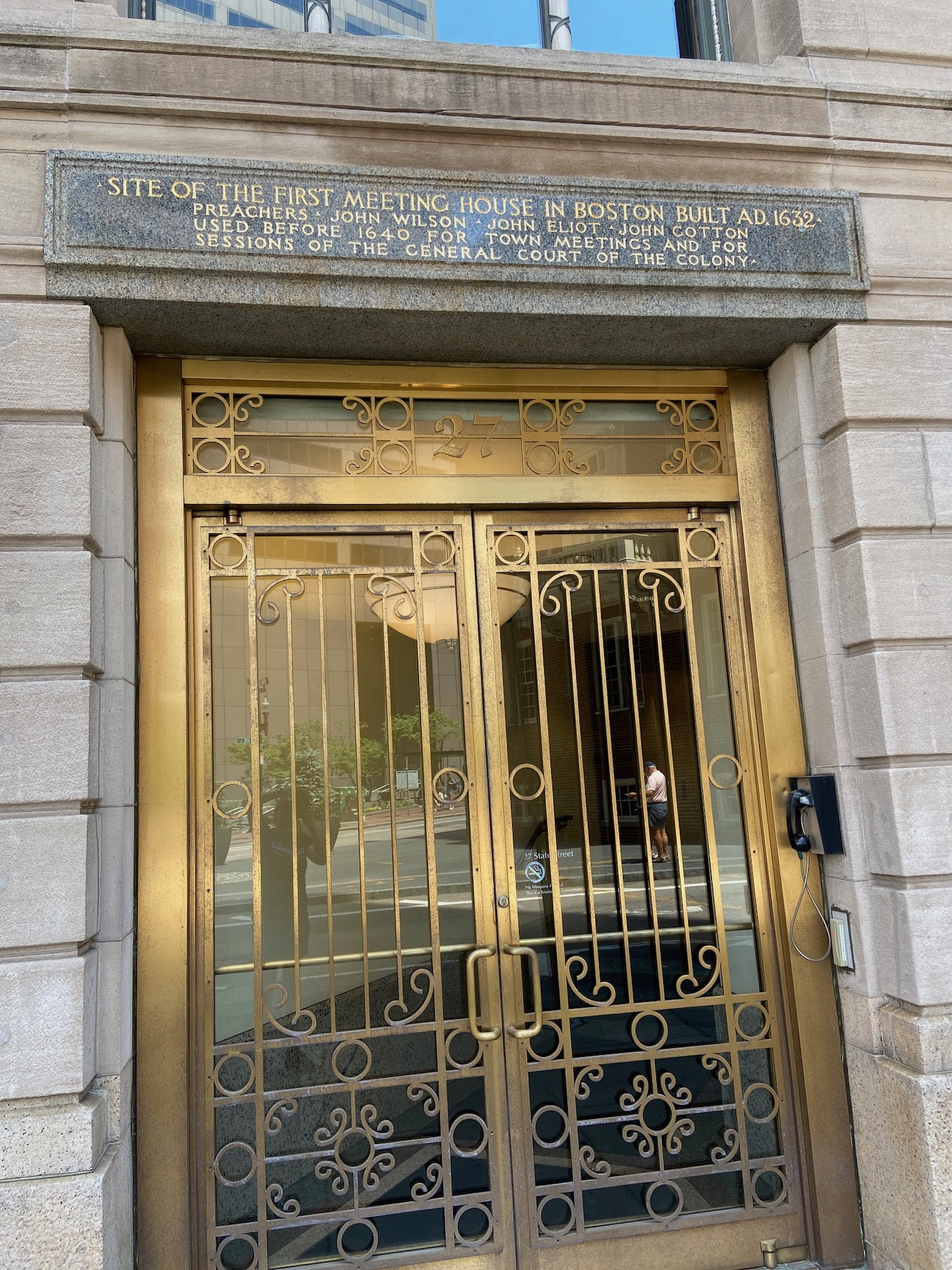 """Image of a building in Boston with golden doors with sign that reads """"SITE of the first meeting house in Boston Build AD 1632"""""""