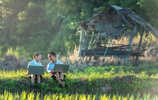 Two children sitting outside on laptops