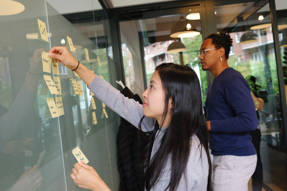 Image of people putting post-it notes on a board