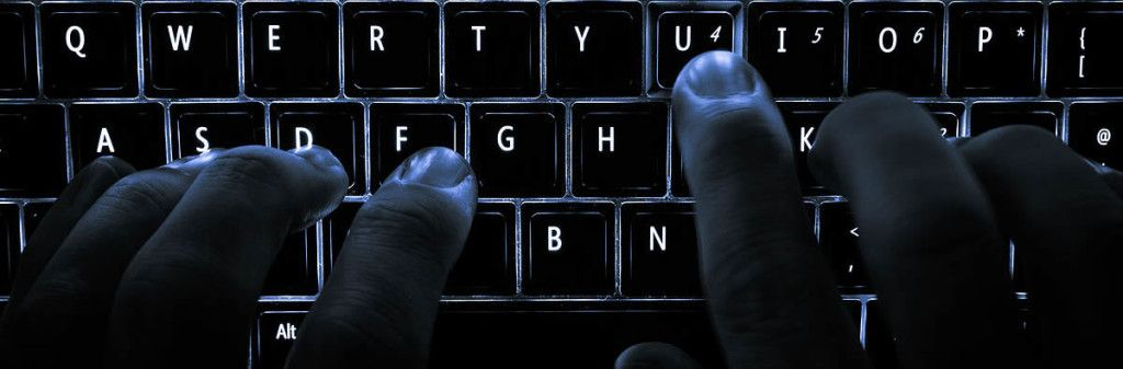 Fingers typing at a keyboard in the dark