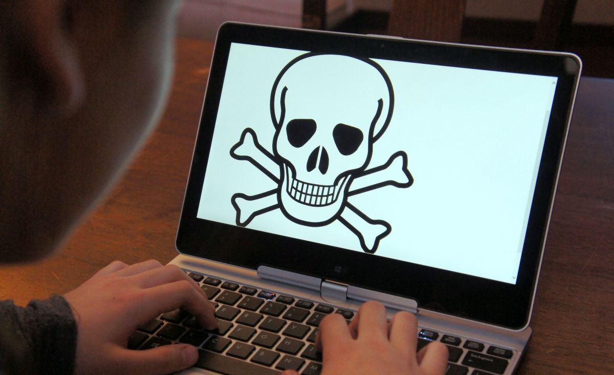 Child at laptop with skull and crossbones on screen