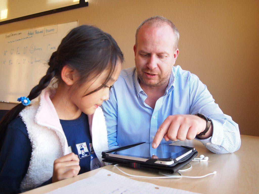 Teacher helping student on iPad