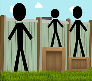 Three people of different heights standing in front of a fence. The two shorter people are standing on top of boxes in order to see over the top of the fence.