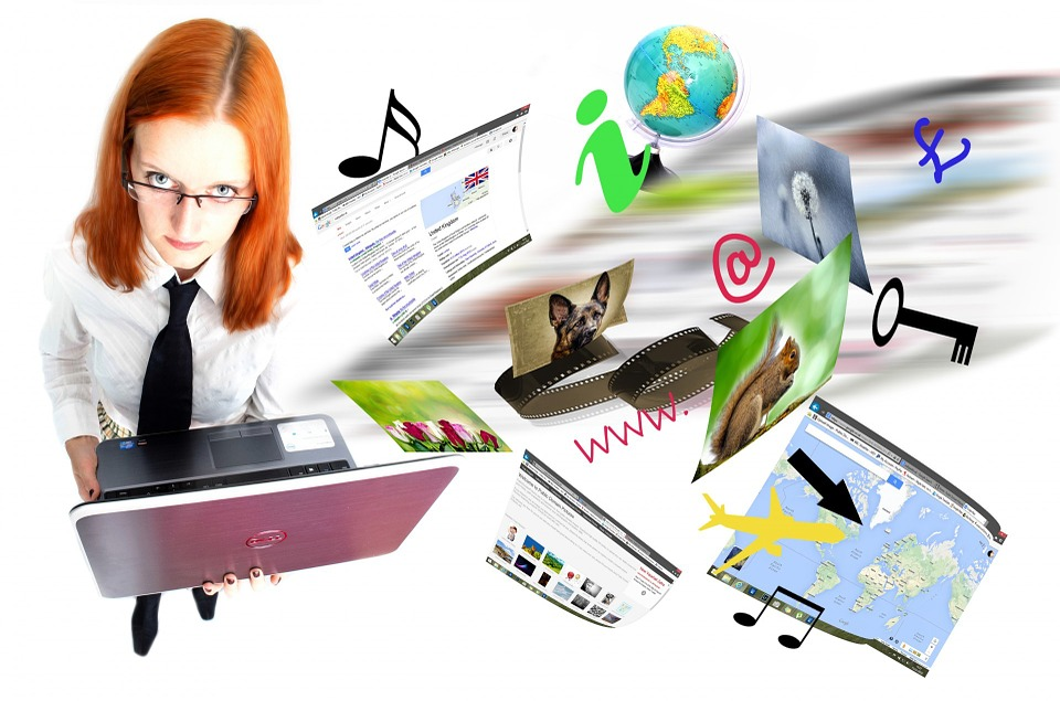 Woman holding laptop with icons floating out of it